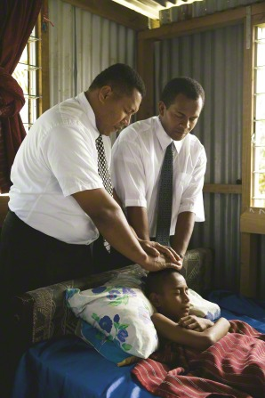 Two men in white shirts and ties give a priesthood blessing to a young boy who is lying sick in bed.