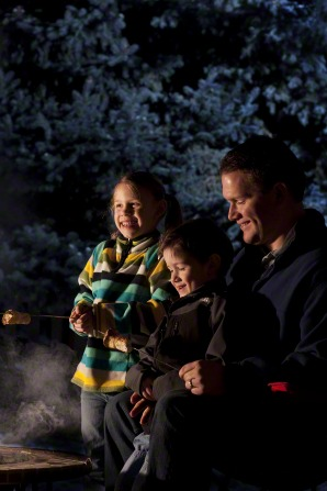 A young father sits with his two small children near a campfire and roasts marshmallows on a stick.