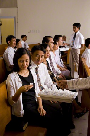 A woman in a white cardigan sweater takes a sacrament cup from a tray that is being held out to her by a deacon.