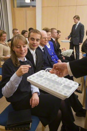 A woman with blond hair reaches out and takes a cup from a sacrament tray held out in front of her.