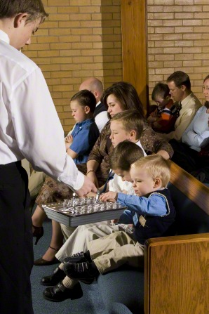 A small boy with blond hair reaches out to take a cup from a metal sacrament tray that a deacon is holding out to him.