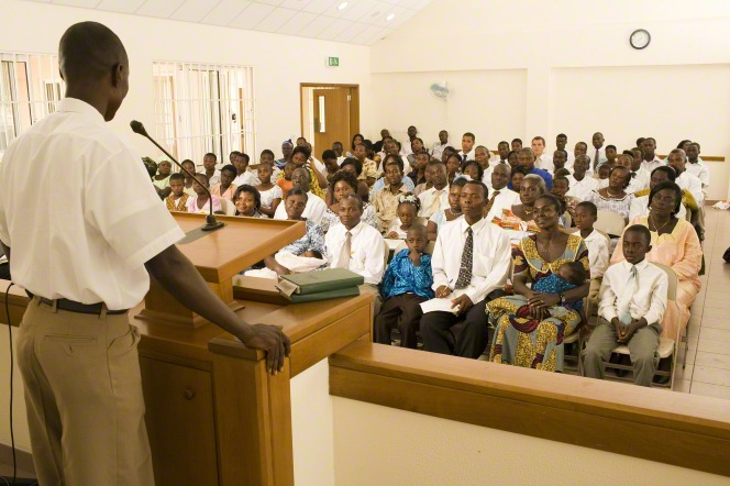 A man in a white shirt stands in front of a large congregation in Ghana and delivers a talk.