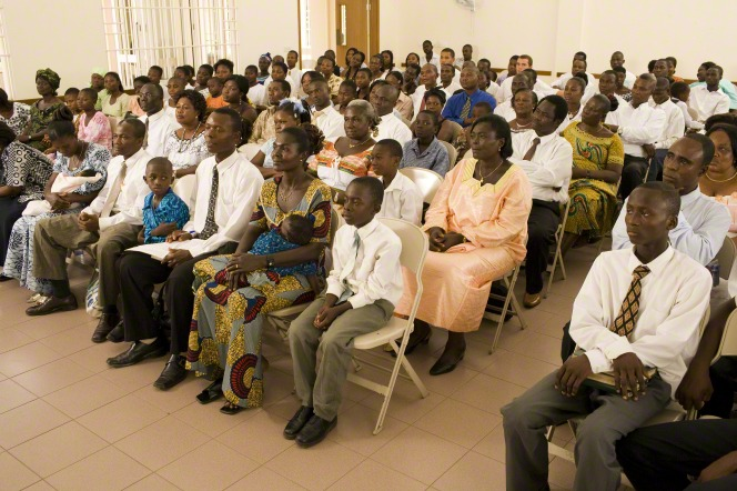 A large congregation of people in Ghana sitting in chairs in their chapel and listening to a speaker.