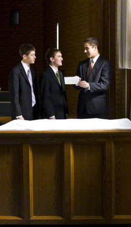 Three young men in suits stand near the sacrament table. One of them uses a printed card to teach the others how to bless the sacrament.