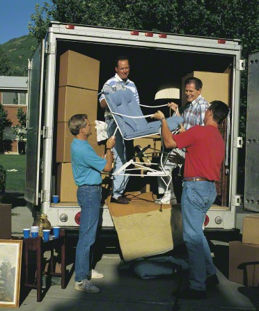 Four men work together to unload a large moving truck, which is filled with cardboard boxes and furniture.