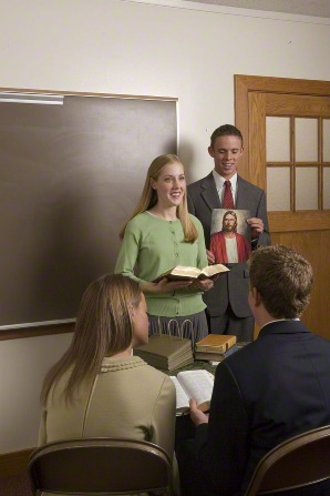 A young woman in a green sweater stands in front of several other people in a Sunday School class, holding her scriptures and speaking.