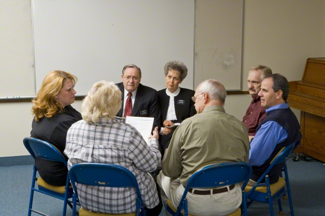 Seven adults, including a missionary couple, sit in a circle learning about Church-service missions.