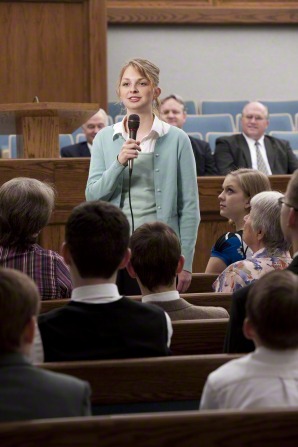 A woman in a green sweater stands in the middle of a congregation and bears her testimony while holding a microphone.