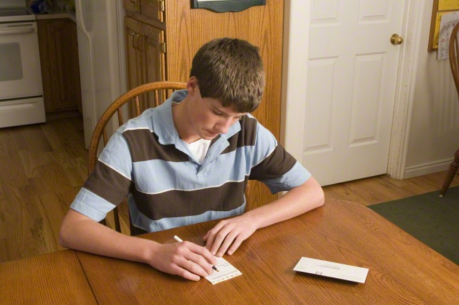A young man in a blue and brown striped shirt sits at the kitchen table and fills out a tithing slip with a pen.