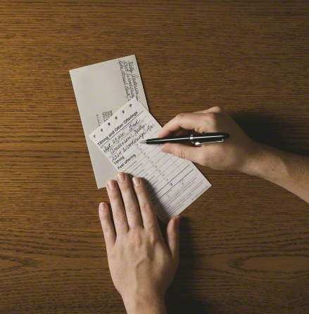 A pair of hands filling out a tithing slip with a black pen.