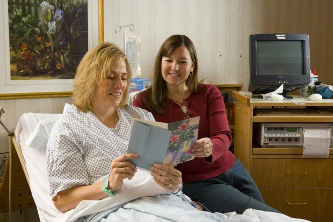 A woman with blond hair is sitting in a hospital bed near a woman who has come to visit and brought her a card with flowers on it.