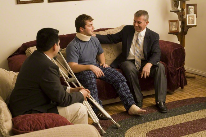 Two men in suits sit and visit with a man who is bandaged and using crutches after an accident.