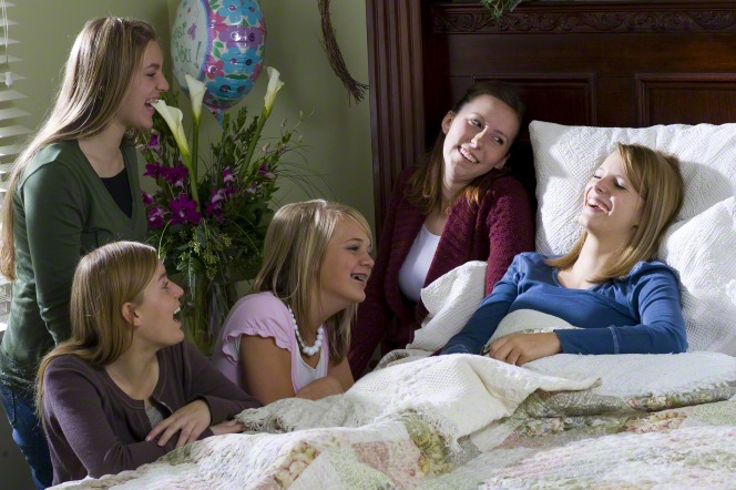A young woman who is sick in bed laughs while her four friends who have come to visit laugh with her.