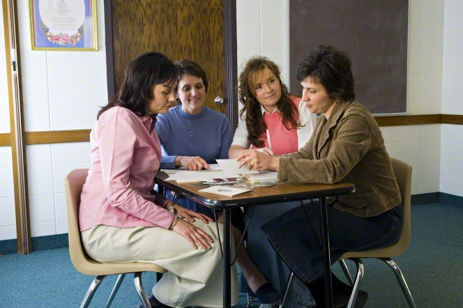 Four women sit in a meetinghouse room, looking at Young Women materials and talking over a list of plans.