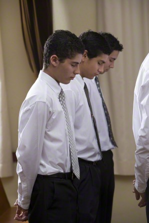 Three young men in white shirts and ties stand and bow their heads while the sacrament prayer is being said.