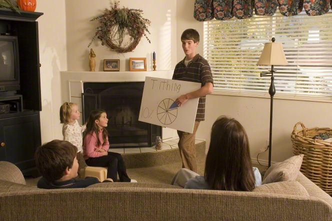 A young man stands in front of his family in their living room, using a poster to teach them about the principle of tithing for family home evening.