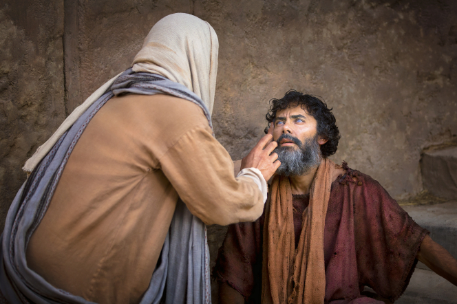 Christ with His hand outstretched, healing a blind man, who is sitting down.