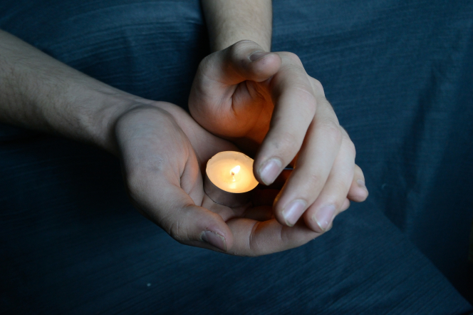 Hands holding a small candle.