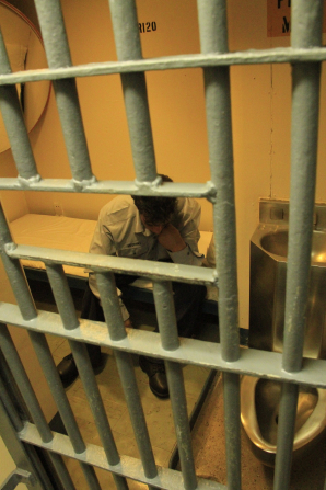 A man sitting in a prison cell, looking discouraged.