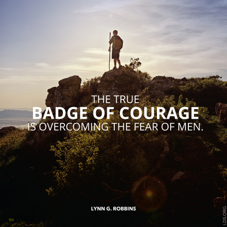 "A photograph of a Scout standing on a mountain, with a quote by Elder Lynn G. Robbins: ""The true badge of courage is overcoming the fear of men."""
