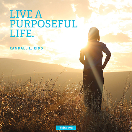 "A photograph of a young woman standing in a field at sunset, with a quote from Randall L. Ridd: ""Live a purposeful life."""