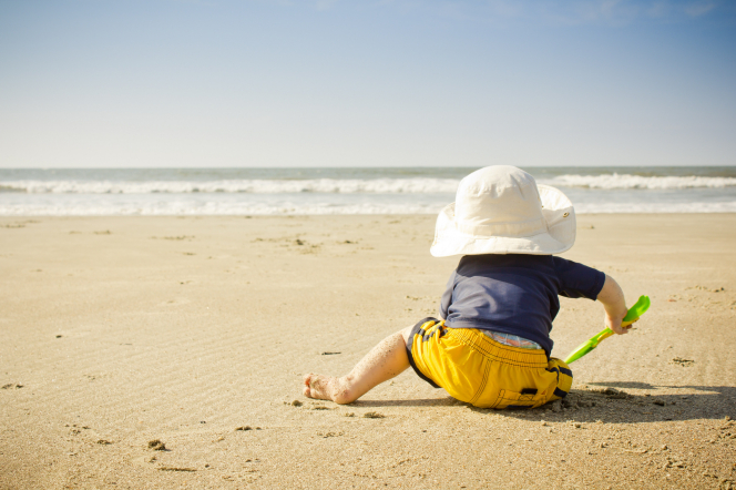 A baby in a sun hat, yellow shorts, and blue shirt plays in the sand with a plastic shovel on the beach.