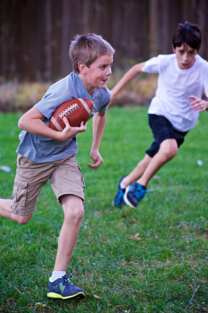 Two boys run through a field while playing football.