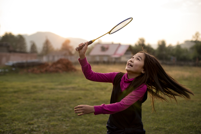 A young girl in Mongolia lifts a racket high in the air while playing badminton outside.