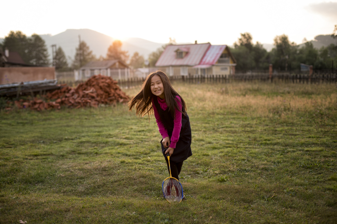 A girl holds a racket close to the ground and smiles during a game of badminton.