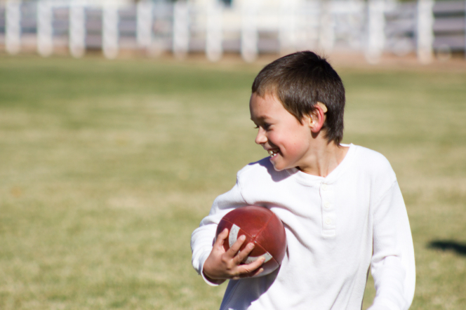 A boy with dark brown hair and a white shirt smiles while holding a football on a grass field.