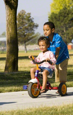 A boy pushes his little sister down the sidewalk while she sits on a tricycle.