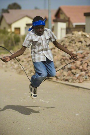 A boy in a plaid shirt and a blue bandanna plays jump rope down a street.