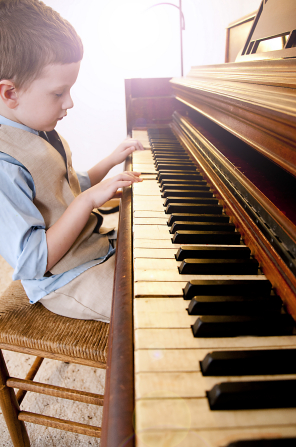 A little boy in a vest sits on a wooden chair and plays on a piano.