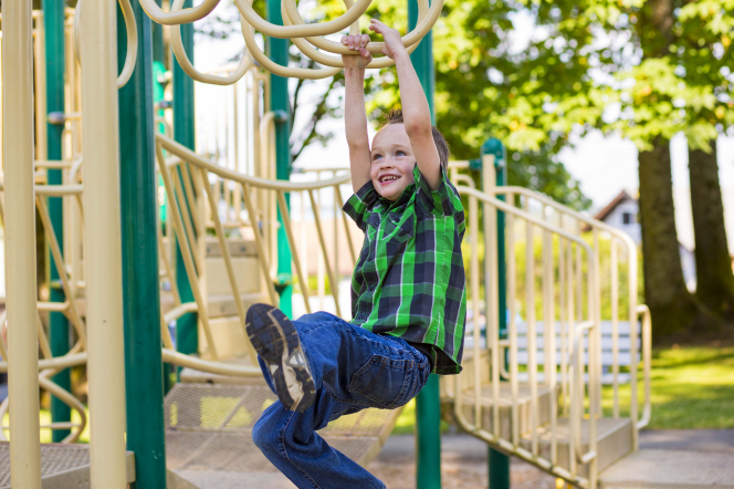 A little boy in a green and blue plaid shirt swings across monkey bars on a playground.