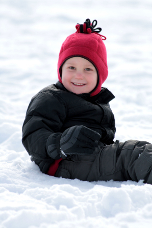A little boy in a black snowsuit, red hat, and black gloves sits down in the snow.