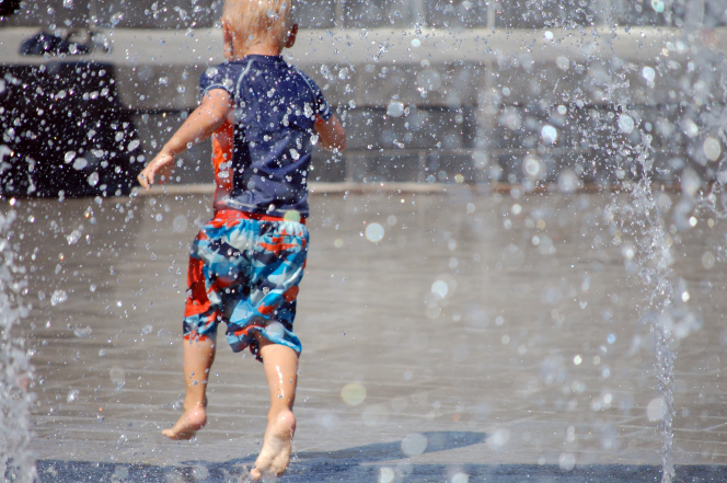 A little boy runs around on a splash pad.