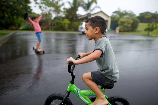 A little boy from New Zealand rides on his green bike through the rain.