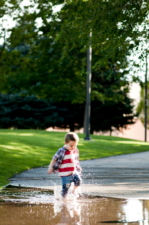 A little boy in an American-flag shirt and blue jeans splashes his feet in a puddle of water on the road.