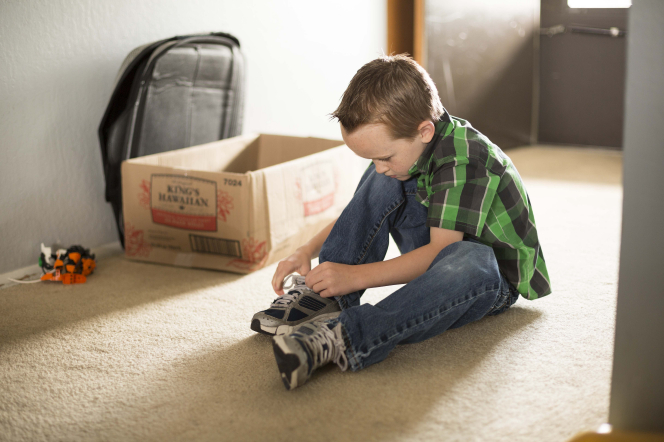 A young boy with brown hair and a green plaid shirt sits on the carpet to tie up his shoelaces.