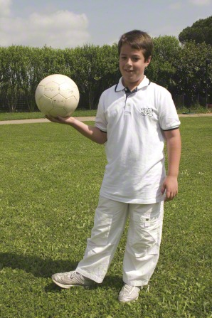 A boy wearing a white shirt, white pants, and white shoes while standing on the grass and holding a white soccer ball in one hand.