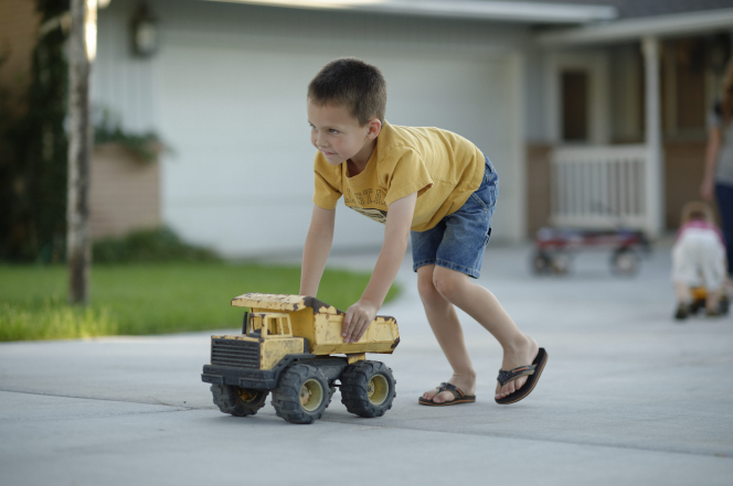 A boy in a yellow shirt, shorts, and flip flops pushes around a yellow toy dump truck in a driveway.