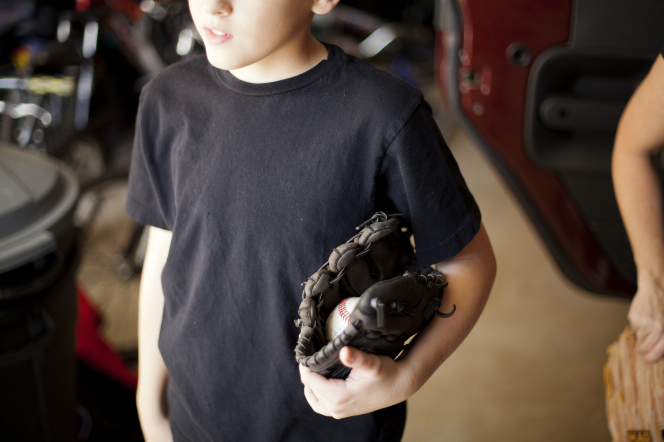 A boy in a black shirt holding a baseball and dark brown mitt under his arm.