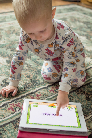 A little toddler in pajamas kneels on the floor and plays on an iPad.