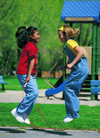 Two girls at a park jumping over a red jump rope while their hair flies up in the air.