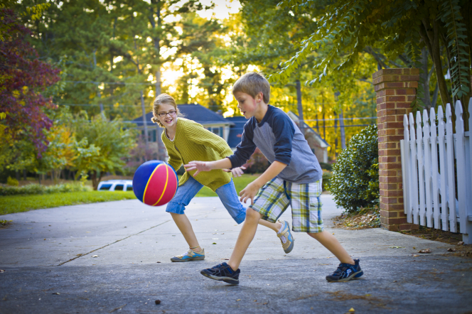 A boy and a girl play with a basketball outside in a driveway.