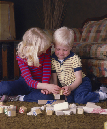 A little boy and girl with blonde hair wearing striped shirts and blue pants and  sitting on brown carpet while playing with wooden blocks.