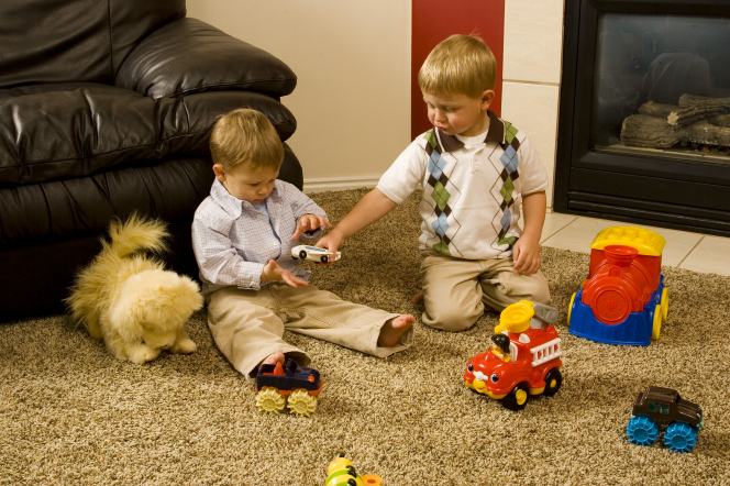 Two little boys play with toy cars while sitting on the living-room floor next to a fireplace and couch.