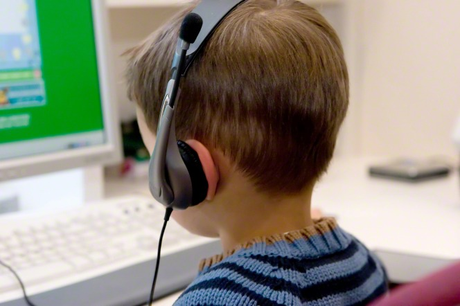A boy in a blue striped shirt wears headphones and plays a game on the computer.