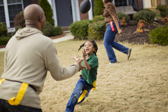A father tosses a football to his daughter while running, and they are both wearing yellow flags around their waists.