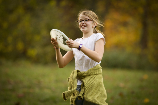 A young girl in glasses and a jacket tied around her waist stands outside and holds a white Frisbee.